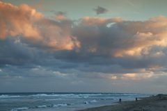 Deerfield Beach, Florida. This is Deerfield Beach, Florida at dusk, facing south with orange clouds above the Atlantic ocean and a few people walking and royalty free stock images