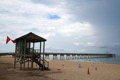 Deerfield Beach Pier Lifeguard Station with Rain Clearing. The rain clouds appear to be passing the Deerfield Beach, Florida Pier with a lifeguard station in the stock image