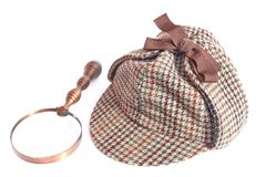 Deerhunter or Sherlock Holmes cap and vintage magnifying glass Royalty Free Stock Images