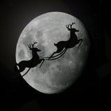 Deers de rêne de Santa volant avec la lune Image libre de droits
