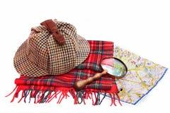 Deerstalker cap, magnifying glass, tartan scarves and London map Royalty Free Stock Images