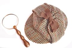 Deerstalker or Sherlock Holmes cap and vintage magnifying glass Royalty Free Stock Photo