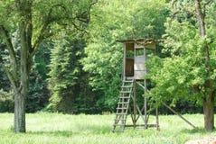 Deerstand que pasa por alto un campo en el bosque negro imagen de archivo libre de regalías