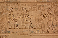 Defaced carving. A large carving on the wall of the Temple of Isis at Philae, Aswan, Egypt. Isis has been defaced as has the image of the Pharoah on the right Stock Photo