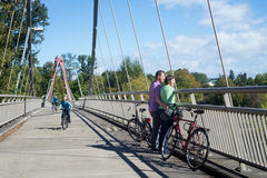 DeFazio Bike Bridge. A couple in their forties take a break on the bike bridge overlooking Alton Baker Park in Eugene Oregon on a beautiful sunny day royalty free stock images
