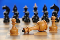 Defeat. Struggle of three white chess figures and black chessmen with its full complement. Low depth of field Royalty Free Stock Photos