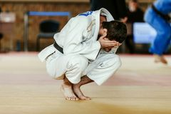 Defeat judoka in white kimono. Is sitting covering face in his hands stock photography