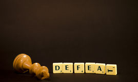 Defeat. Made out of word tiles with knocked over white king isolated on white Royalty Free Stock Photo