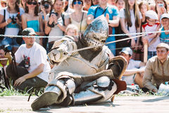 Defeated In Battle Knight Tries To Get Up From The Floor. Dudutki, Belarus - July19, 2014: Historical restoration of knightly fights on festival of medieval Stock Image