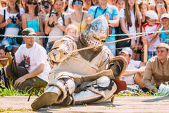 Defeated In Battle Knight Tries To Get Up From The Floor. MINSK, BELARUS - JULY 19, 2014: Historical restoration of knightly fights on VI festival of medieval Stock Images
