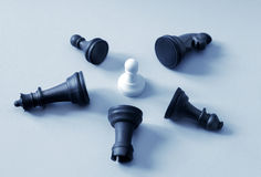 Defeated black chess pieces and consisting of white pawn Stock Photos