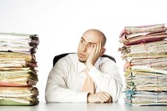 Defeated Man. Man looks to be defeated by the piles of paperwork that flank him on either side.  Model is adult male and bald.  He has a short beard and is Stock Images