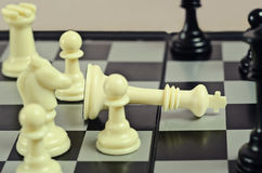 Defeated white king. White defeated chess king lying on the black-and-white board surrounded by other figures Royalty Free Stock Photo