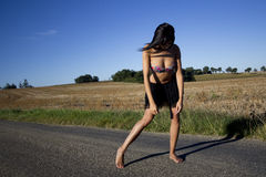 Defeated woman walking barefoot on a road. Defeated attitude of a young woman on a country road. She is barefoot and she looks down. In the background stubble Royalty Free Stock Photo