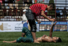 A defeated wrestler is handed a water bottle at the Kemer Turkish Oil Wrestling Festival in Turkey. Royalty Free Stock Photo