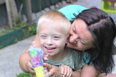Mother and son with down syndrome. Defect,childcare,medicine and people concept- happy mother and son with down syndrome playing in a garden Stock Photography