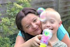 Mother and son with down syndrome. Defect,childcare,medicine and people concept- happy mother and son with down syndrome playing in a garden Stock Image