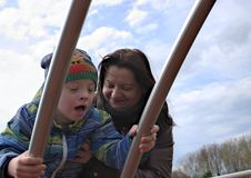 Mother and son with down syndrome. Defect,childcare,medicine and people concept- happy mother and son with down syndrome playing in a playground Stock Photography