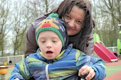 Mother and son with down syndrome. Defect,childcare,medicine and people concept- happy mother and son with down syndrome playing in a playground Royalty Free Stock Photography