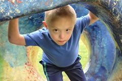 Boy with a down syndrome who is playing in a park. Defect,childcare,medicine and people concept- young boy with a down syndrome who is playing in a park stock photos