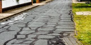 Defective and constantly repaired asphalt on a village road Stock Photos