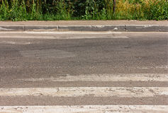 Defective pedestrian crossing, with worn out stripes Stock Images