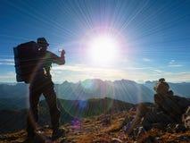 Defecto de la llamarada de la lente La guía turística en pico de las montañas toma la foto Caminante fuerte con la mochila grande Fotografía de archivo libre de regalías