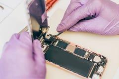 Defekt mobiltelefon för teknikerreparation i elektronisk smartphone t Arkivbild