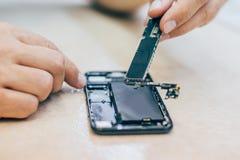 Defekt mobiltelefon för teknikerreparation i elektronisk smartphone t Royaltyfri Foto