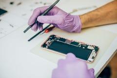 Defekt mobiltelefon för teknikerreparation i elektronisk smartphone t Royaltyfri Bild