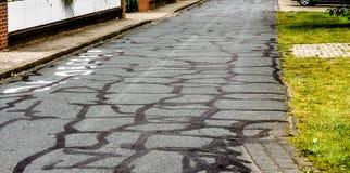 Defekt och ständigt reparerad asfalt på en byväg Arkivfoton