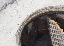 Defekte Abwasserkanalluke, öffnen Abflussluke stockfotos