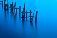 Defekte Anlegestelle auf ruhigem Wasser. Stockbild