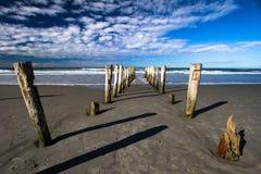 Defekte Anlegestelle, die heraus zu den Seealten Anhäufungen gelassen im Sand schaut Lizenzfreies Stockfoto