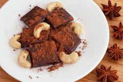 Defekte dunkle Schokolade mit Kakaopulver- und Acajounüssen und Sternanis stockbild