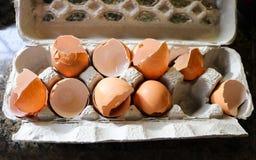 Defekte Eierschalen von den Eiern benutzt für das Kochen in Papier-mache Eierkarton auf Marmorcountertop Stockbilder