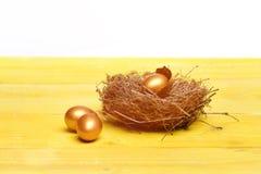 Defekte goldene Eier Ostern mit Oberteil im Vogel nisten Stockbilder