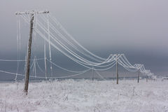 Defekte Phasenelektrische leistung zeichnet mit Reif auf den hölzernen elektrischen Pfosten auf Landschaft im Winter nach Sturm stockfoto
