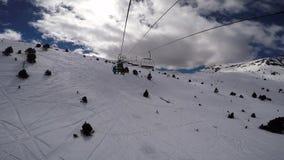 Defekte Skiaufzugskifahrer, die warten, als es regelte stock video footage