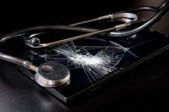 Defekte Tablette mit defektem Schirm und Stethoskop in der Reparatur Blac Lizenzfreies Stockbild