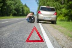 Defekter Auto- und Mannesfahrer, der das Rad ändert stockfoto