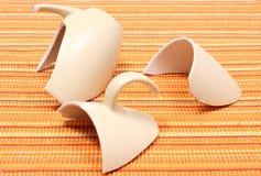 Defekter Becher, zerbrochene Schale auf orange Stoff Stockfotografie