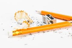 Defekter Bleistift mit Metallbleistiftspitzer und -schnitzeln Stockfotografie