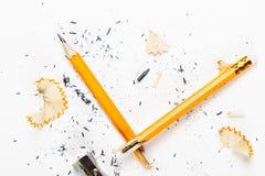 Defekter Bleistift mit Metallbleistiftspitzer und -schnitzeln Lizenzfreie Stockfotografie