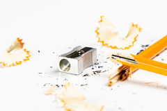 Defekter Bleistift mit Metallbleistiftspitzer und -schnitzeln Stockbild