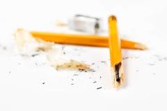 Defekter Bleistift mit Metallbleistiftspitzer und -schnitzeln Lizenzfreie Stockbilder