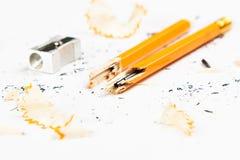 Defekter Bleistift mit Metallbleistiftspitzer und -schnitzeln Lizenzfreies Stockbild