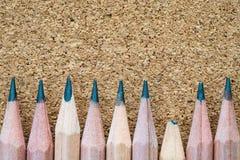 Defekter Bleistifttipp dazu von anderen scharfen auf Spanplatten-Beschaffenheitshintergrund mit Kopienraum Stockfotos