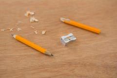 Defekter gelber Bleistift mit Bleistiftspitzer Lizenzfreies Stockfoto