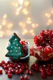 Defekter Granatapfel, Samen, Lebkuchen-Plätzchen und Weihnachtslichter Stockbilder